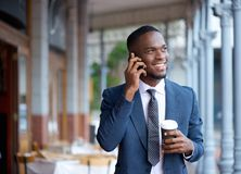 Smiling businessman walking and talking on mobile phone Stock Images