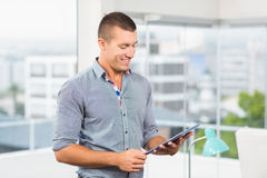 Smiling businessman watching at his tablet Stock Photography