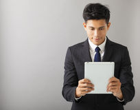 Smiling businessman watching the tablet pc. Young smiling businessman watching the tablet pc Royalty Free Stock Image