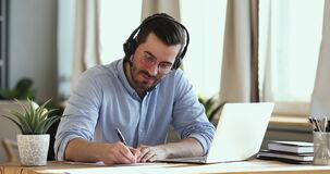 Smiling businessman wear headset making conference video call on laptop