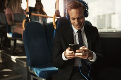 Smiling businessman wearing headphones and reading texts on a bu stock images