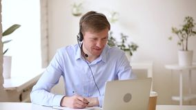 Smiling businessman wearing headset studying online making notes