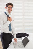 Smiling businessman wearing tie while using laptop at hotel room Stock Photo