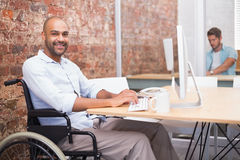 Smiling businessman in wheelchair working at his desk Stock Images