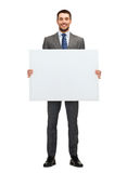Smiling businessman with white blank board Royalty Free Stock Photos