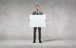 Smiling businessman with white blank board Stock Photo