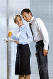 Smiling businessman with woman holding glass of coffee and newspaper in office Stock Photo