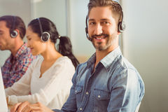 Smiling businessman working in a call centre Stock Images