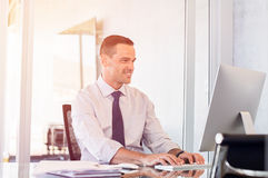 Smiling businessman working on computer royalty free stock photography