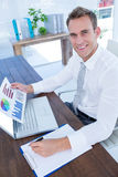 Smiling businessman working with flow charts. Portrait of a smiling businessman working with flow charts stock image
