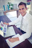 Smiling businessman working with flow charts. Portrait of a smiling businessman working with flow charts royalty free stock images