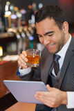 Smiling businessman working on his tablet while having a whiskey Stock Image