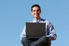 Smiling businessman working on laptop Stock Photo