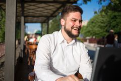 Smiling Businessman Working on Laptop at Cafe Royalty Free Stock Photography
