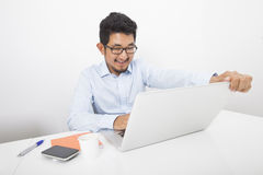 Smiling businessman working on laptop at desk in office Royalty Free Stock Photos