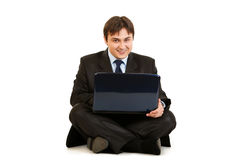 Smiling businessman working on laptop on floor Stock Photos