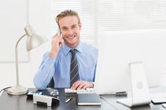 Smiling businessman working and phoning at his desk Stock Images