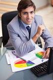 Smiling businessman working on statistics Stock Images