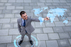Smiling businessman with world map projection Royalty Free Stock Image