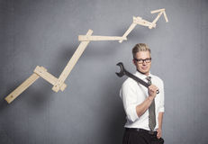 Smiling businessman with wrench and graph. Concept: Building your own successful career or business. Smiling confident businessman holding  wrench in front of Stock Photo