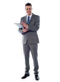 Smiling businessman writing on clipboard Royalty Free Stock Images
