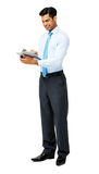Smiling Businessman Writing On Clipboard Stock Photography