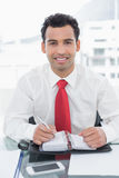 Smiling businessman writing in diary at office. Portrait of a smiling young businessman writing in diary at a bright office Royalty Free Stock Image