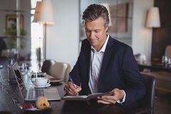 Smiling businessman writing on diary. At restaurant Royalty Free Stock Image