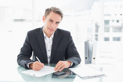 Smiling businessman writing documents at office desk Royalty Free Stock Image