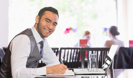 Smiling businessman writing while looking at camera Stock Photo