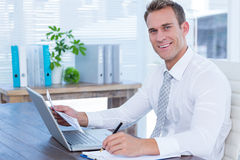 Smiling businessman writing on notebook Stock Image