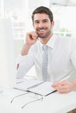 Smiling businessman writing on notepad Stock Photography