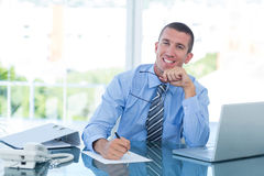 Smiling businessman writing notes Royalty Free Stock Image