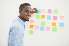 Smiling businessman writing on sticky notes Royalty Free Stock Photo