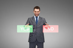 Smiling businessman with yes and no buttons. Business, technology, choice and people concept - smiling businessman with yes and no buttons Stock Image