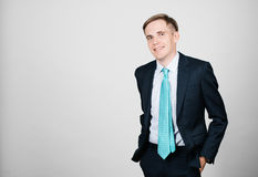 Smiling businessman. Young and handsome smiling businessman standing, shot on bright background Stock Photos