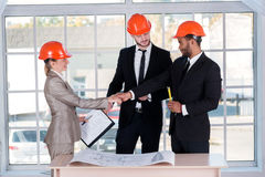 Smiling businessmen architects shaking hands. Three businessman Stock Photography