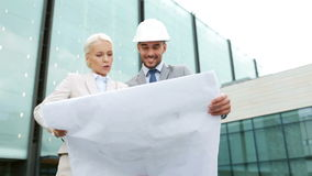 Smiling businessmen with blueprint and helmets Stock Image