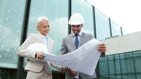 Smiling businessmen with blueprint and helmets Royalty Free Stock Images