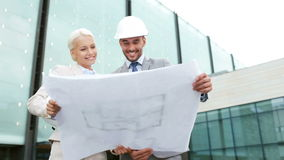 Smiling businessmen with blueprint and helmets Stock Photos
