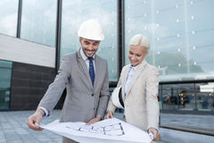 Smiling businessmen with blueprint and helmets Royalty Free Stock Photo