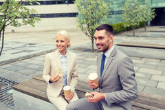 Smiling businessmen with paper cups outdoors Stock Image