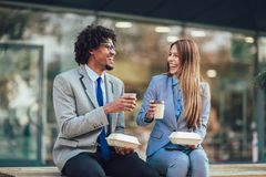 Smiling businessmen with paper cups sitting in front of the office building royalty free stock image