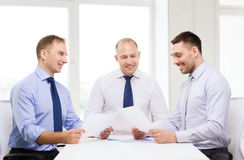 Smiling businessmen with papers in office Stock Image