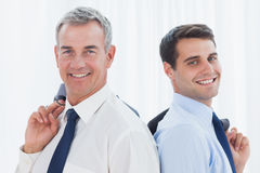 Smiling businessmen posing back to back together while holding t. Smiling businessmen in bright office posing back to back together while holding their jacket Royalty Free Stock Images