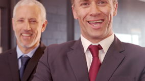Smiling businessmen posing with crossed arms. In the office stock video