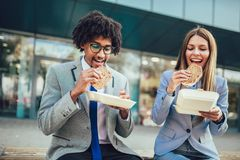 Smiling businessmen with sandwiches sitting in front of the office building stock photography