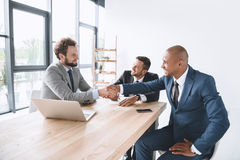 Smiling businessmen shaking hands at meeting at workplace with laptop. Multiethnic smiling businessmen shaking hands at meeting at workplace with laptop Royalty Free Stock Image
