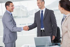 Smiling businessmen standing and shaking hands Stock Photos