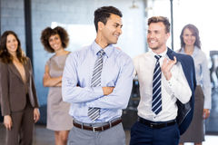 Smiling businessmen standing together in front and businesswomen standing in background. Smiling businessmen standing in front while businesswomen standing Royalty Free Stock Photos